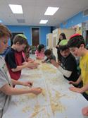Fourth graders at Shomrei Emunah make  Matzah from scratch.